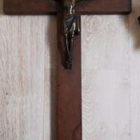 een houten kruis met koperen corpus