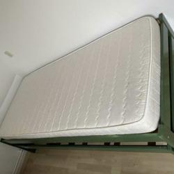 Het is een geverfd groen uitschuifbaar bed