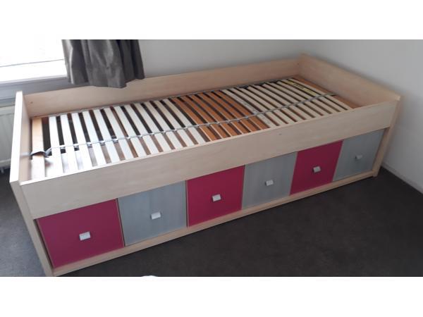 Eenpersoonsbed met kastjes en lades onderin. Inclusief lattenbodem